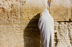 A religious orthodox Jew wearing a prayer shawl draped prays at the western wall. Jerusalem, Israel.